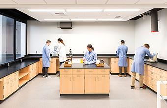 4. Four students and the professor work with equipment at lab benches with ample space around and above them