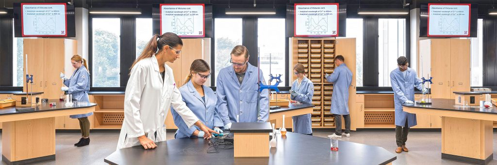 Chemistry professor demonstrating use of equipment to two students in a modern teaching laboratory