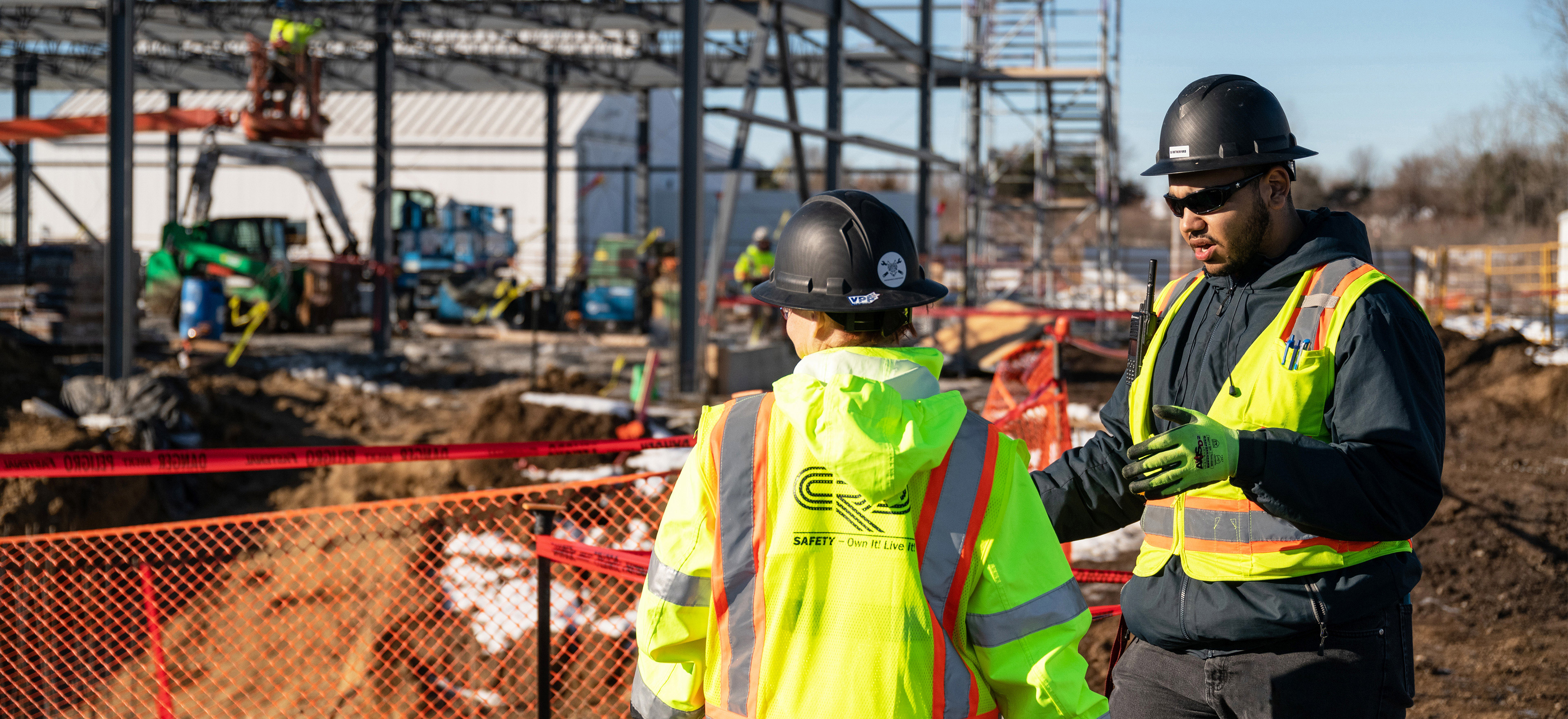 two CRB construction employees talking on the job site