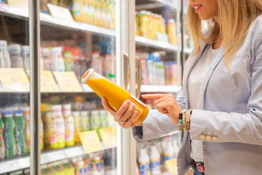 consumer inspects food label in grocery store